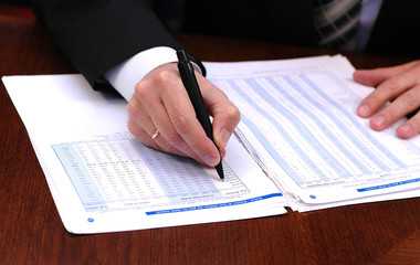businessman is writing financial report