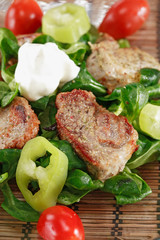small steaks with salad and vegetable