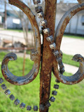 wraught iron, rust,, and mardi gras beads poster