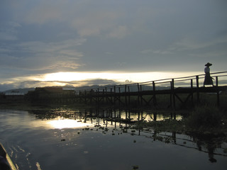 sunset over the teck bridge with a walking man, inle lake, myanm