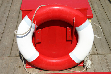 a red and white lifebelt/lifebuoy on a boat deck.