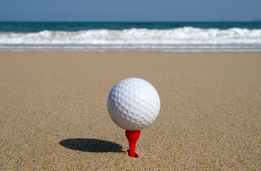 golf ball on the beach, ready to be hit in to the