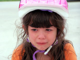 child crying while wearing a bike helmet poster