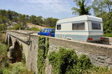 car with trailer (camper) on a bridge in france poster