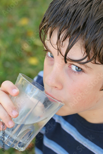 boy drinking a glass of water vertical
