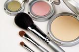 three makeup brushes and blush