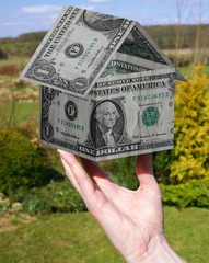 hand holding $1 house