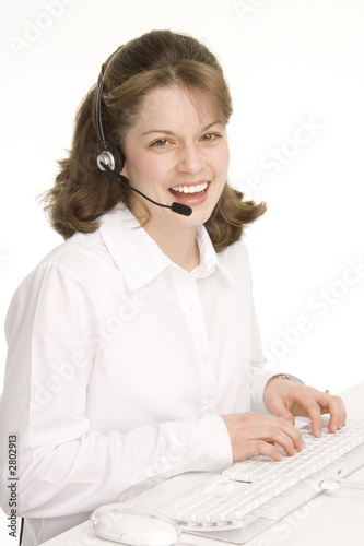 receptionist with headphones, smiling, keyboard