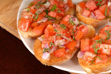 tomato and onion bruschetta with thyme on cutting board