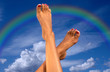 legs over sky with clouds and rainbow