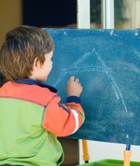 boy painting on a blackboard