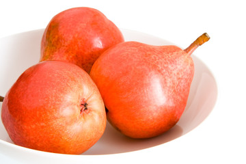 three red pears on a plate