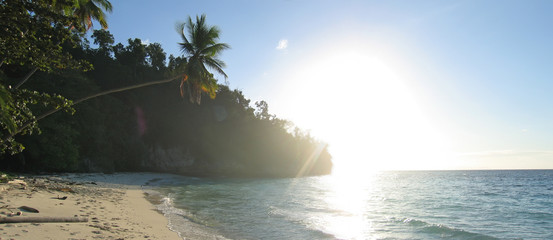 tropical beach with facing sun, togians island, sulawesi, indone