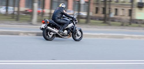 leather dressed biker on chrome chopper bike speed