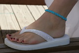 white sandal foot polished nail ankle bracelet poster
