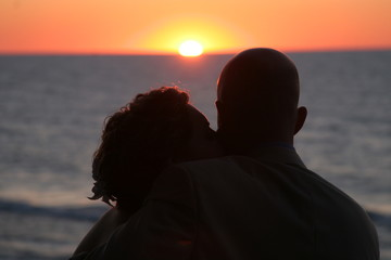 silhouette couple with sun setting over ocean