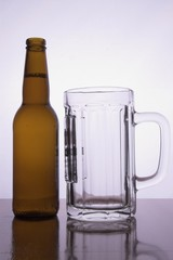a bottle of cold beer with no lables and a pitcher