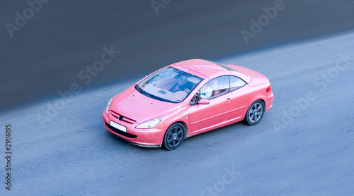 Foto op Canvas Snelle auto s woman driving small pink coupe car fast speed