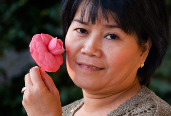 asian woman holding a flower
