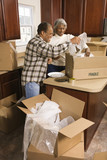 middle-aged couple unpacking boxes. poster