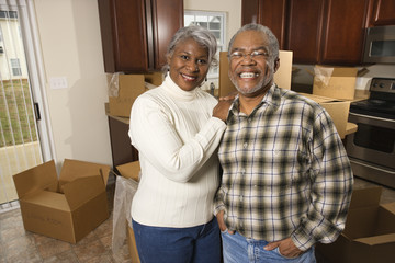 middle-aged couple standing in kitchen with boxes.