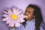 african-american man biting big fake purple flower. poster