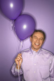 caucasian man holding purple balloons. poster