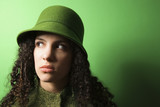 young caucasian woman wearing green clothing and hat. poster