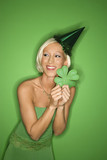 young caucasian woman wearing party hat and holding shamrock. poster