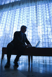 businessman sitting on bench typing on laptop. poster