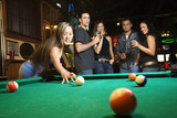 young female preparing to hit pool ball. poster