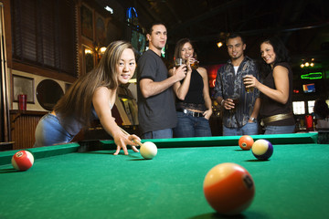 young female preparing to hit pool ball.