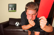 referee in sitting room blowing whistle with red c