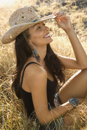 young woman wearing a straw cowboy hat.