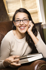 smiling woman in a chair holding a book.