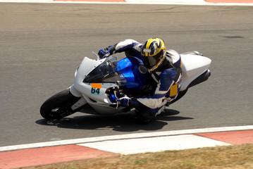close-up of a biker on a superbike on track.