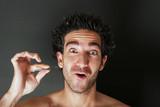 man pulling his beard with tweezer poster