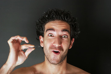 man pulling his beard with tweezer