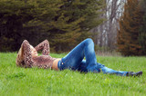 cheerful girl laying on the grass poster