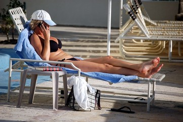 woman sunbather on cell phone