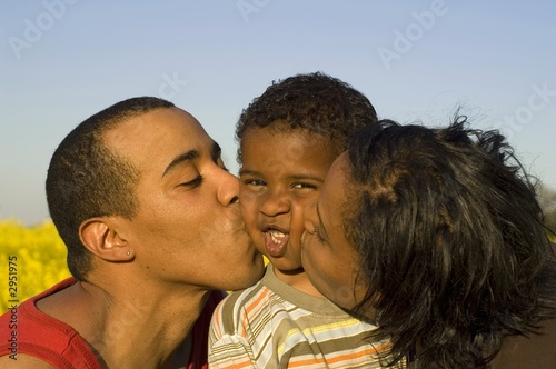 parents kissing their cute little son