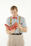 young man dressed like nerd reading book.