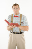 young man dressed like nerd with book open.