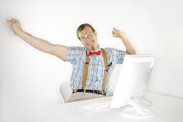 young man stretching arms out at computer.