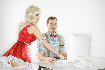 young man sitting at computer with young woman