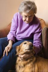 elderly caucasian woman petting dog.