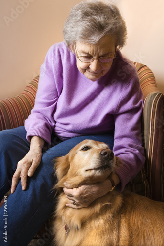 elderly caucasian woman petting dog.
