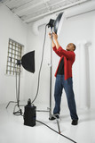 young male adjusting studio lights. poster