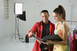 young male photographer and young female model looking at portfo
