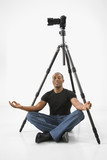 young male adult meditating under camera and tripod. poster